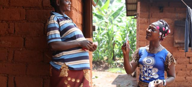 Community worker, Chacha Anita Ngwanchu (right) makes a house visit to encourage vaccinations at the local health facility